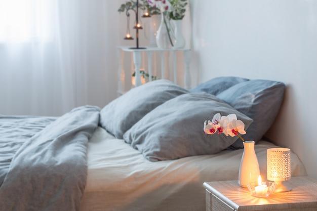 Orched bloemen in vaas en brandende kaarsen in witte slaapkamer