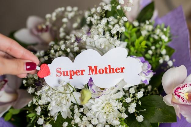 Orchideebloemen en bloemen cadeau voor moeder. het concept van happy mother's day. bericht in vrouwelijke hand, super moeder. wit blad met rood hart en super moeder tekst.