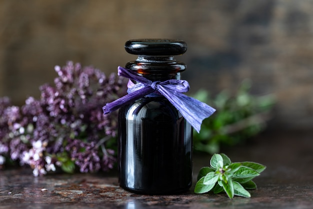 Oregano etherische olie in glazen fles op houten oppervlak