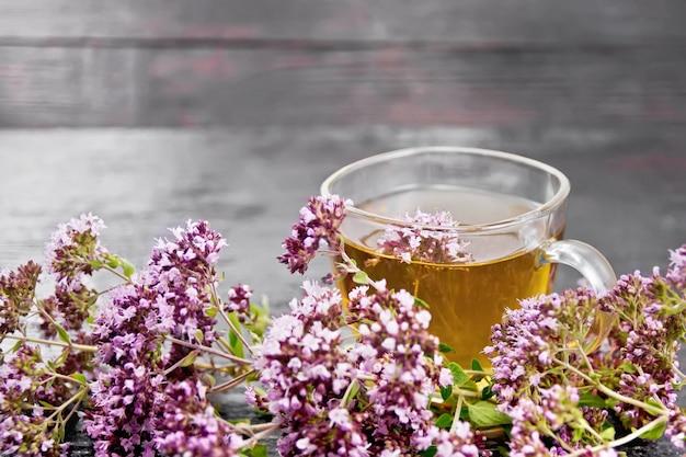 Oregano kruidenthee in een glazen beker, verse roze marjolein bloemen op donkere houten bord