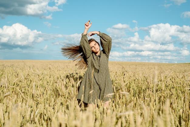 Oren van tarwe. jong meisje in jurk toont emotie. springt emotioneel en rent op een zomerveld met aartjes.