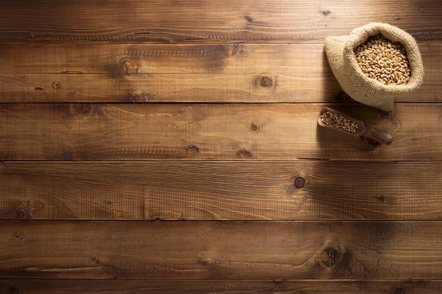 Oren van tarwe op houten textuur als achtergrond