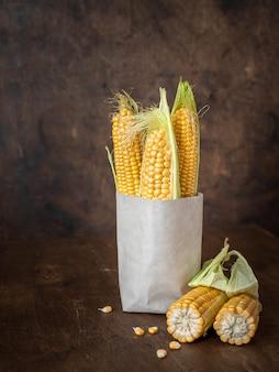 Oren van verse maïs in een papieren zak