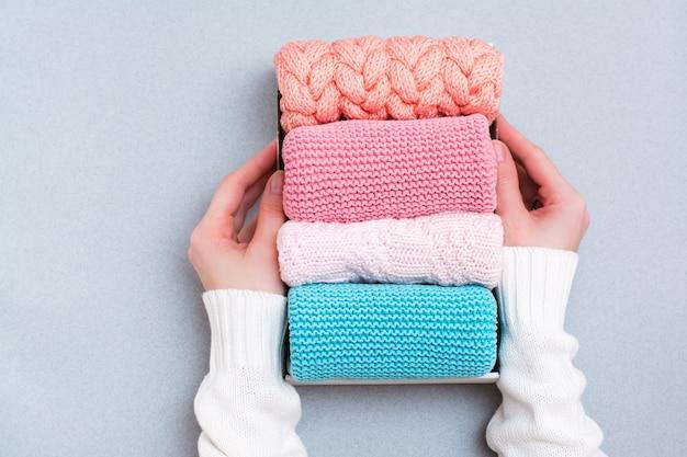 Organisatie en orde. de handen van vrouwen houden een doos netjes opgevouwen gebreide kleding vast.