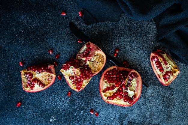 Organisch rijp granaatappelfruit op zwarte steenlijst