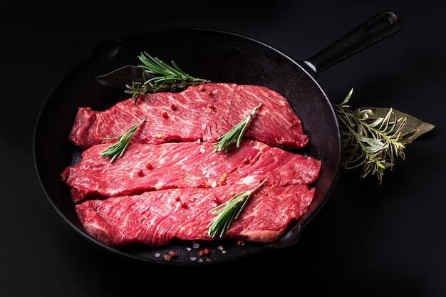 Organisch ruw het vleesfilethaakwerklapje vlees van het voedselconcept in de pan van het koekepanijzer op zwarte