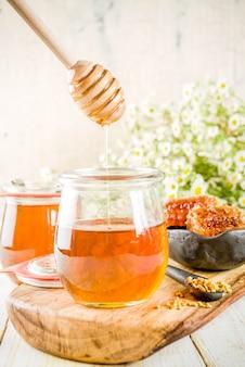 Organische bloemenhoning, in potten, met stuifmeel en honingkammen, op een witte houten tafel, met wilde bloemen