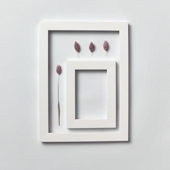 Organische compositie van dennenappels en rechthoekig leeg frame voor uw tekst op een lichtgrijze muur. bovenaanzicht.