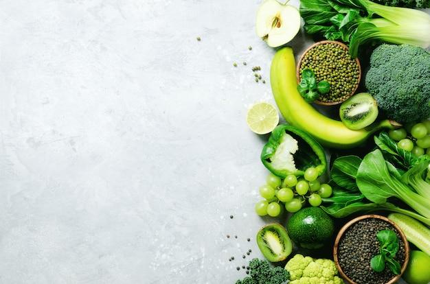 Organische groene groenten en fruit op grijs. ruimte kopiëren, plat leggen, bovenaanzicht. groene appel, courgette, komkommer, avocado, boerenkool, limoen, kiwi, druiven, banaan, broccoli, gemarmerde linzen, mungboon