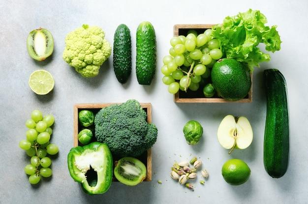 Organische groene groenten en fruit op grijs. ruimte kopiëren, plat leggen, bovenaanzicht. groene appel, sla, courgette, komkommer, avocado, boerenkool, limoen, kiwi, druiven, banaan, broccoli