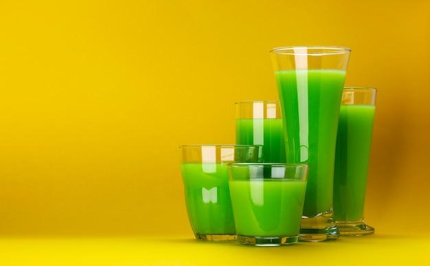 Organische groene smoothieglazen die op gele achtergrond worden geïsoleerd