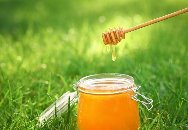 Organische honing die van honingsdipper druipt op natuurlijke groene achtergrond.