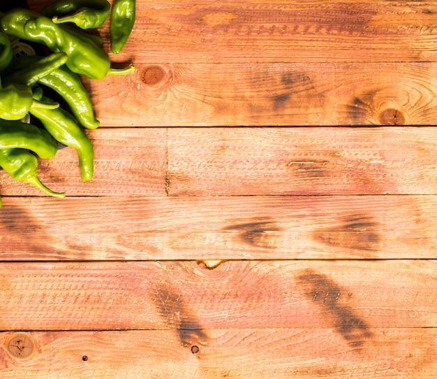 Organische lange groene paprika's op houten achtergrond. bovenaanzicht
