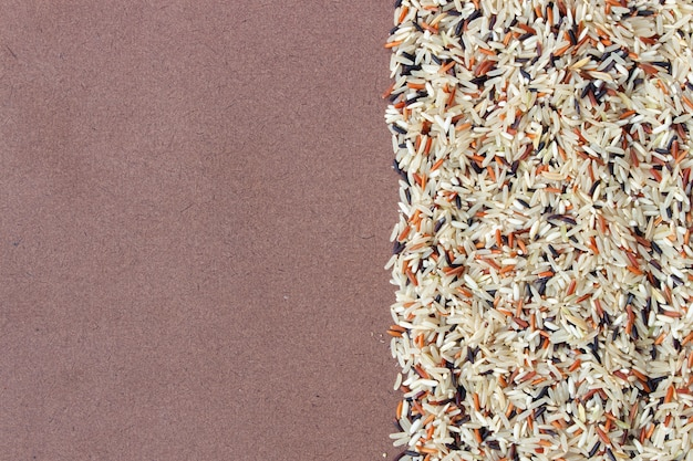 Organische rijstbes, rode jasmijnrijst en ongepelde rijst (hommalirijst) op houten achtergrond