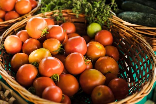 Organische rode tomaten rieten mand bij kruidenierswinkelopslag