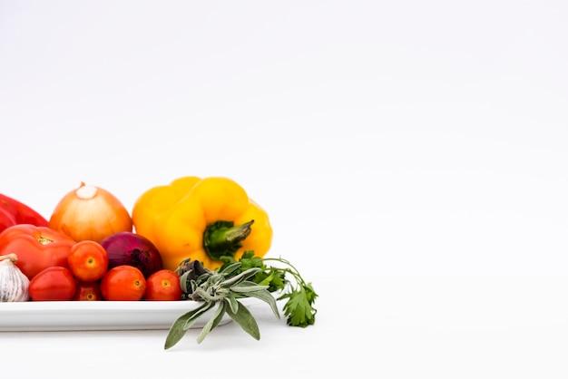 Organische verse groenten in dienblad dat op witte achtergrond wordt geïsoleerd
