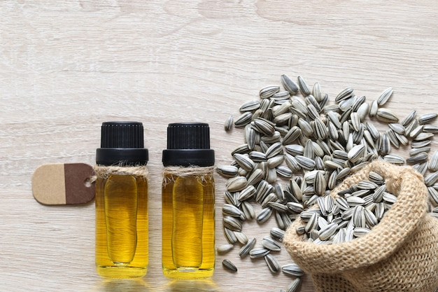 Organische zonnebloemolie in glazen flessen en zonnebloemzaad op hout