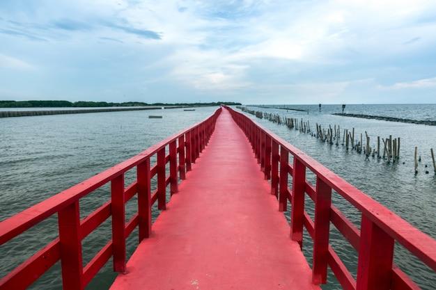 Oriëntatiepuntarchitectuur in reizen op rode brug aan oceanside
