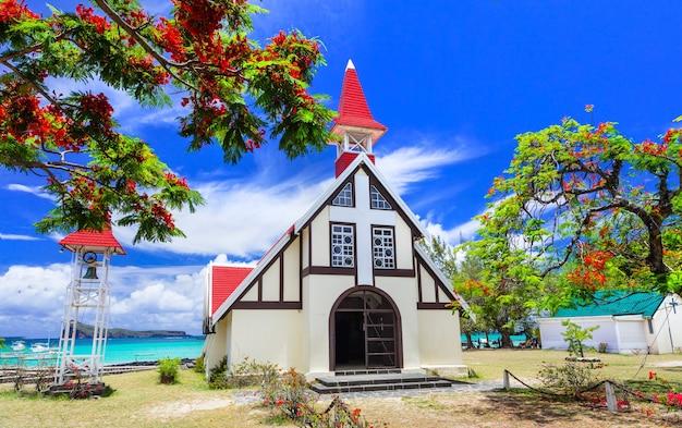 Oriëntatiepunten van het prachtige eiland mauritius - rode kerk met bloeiende flamboyante boom