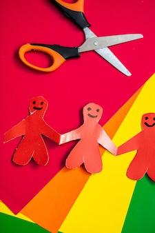 Origami in de vorm van mannen die elkaars hand vasthouden op een achtergrond van veelkleurig papier