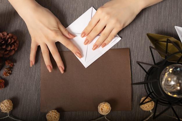 Origami is een oude chinese kunst van het vouwen van papier. meisje maakt een beeldje op een gezellige bruine achtergrond met lichtjes en een warme lamp