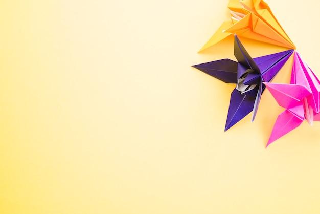 Origami kleurrijke papieren bloemen op gele achtergrond