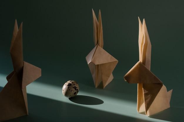 Origami papier konijn, kwarteleitjes op in de felle zon met harde schaduwen. minimalistisch modern pasen-concept. heldere pasen-achtergrond.