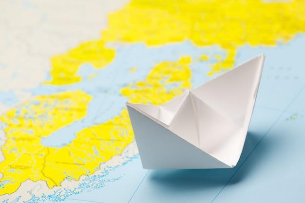 Origami papier schip op een kaart.
