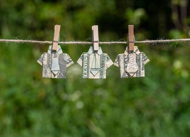 Origami shirt gemaakt van dollar biljet op hangende groene natuur achtergrond
