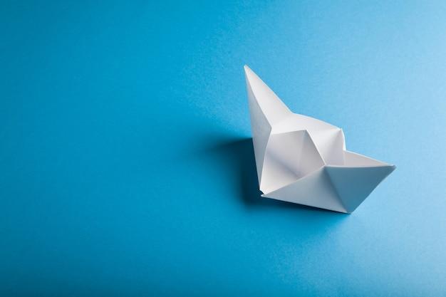 Origamibootpapier op het blauwe oppervlak