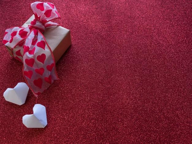 Origamidocument harten vormen symbolen voor valentijnsdag, met een geschenkdoos met rood lint. kopieer ruimte voor tekst of ontwerp