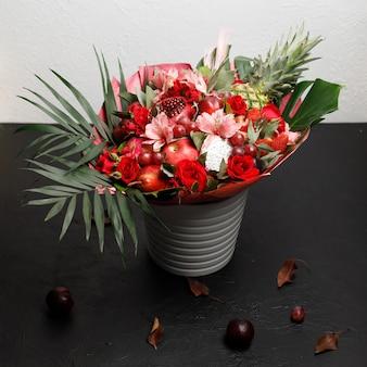 Origineel ongebruikelijk boeket rozen, orchideeën en diverse rode vruchten op een zwarte achtergrond