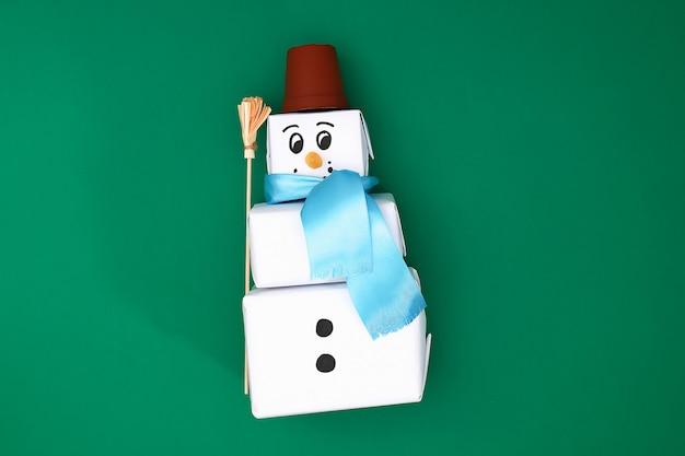 Origineel ontwerp van de drie kerstgeschenken van wit papier, een satijnen lint in de vorm van een sneeuwpop