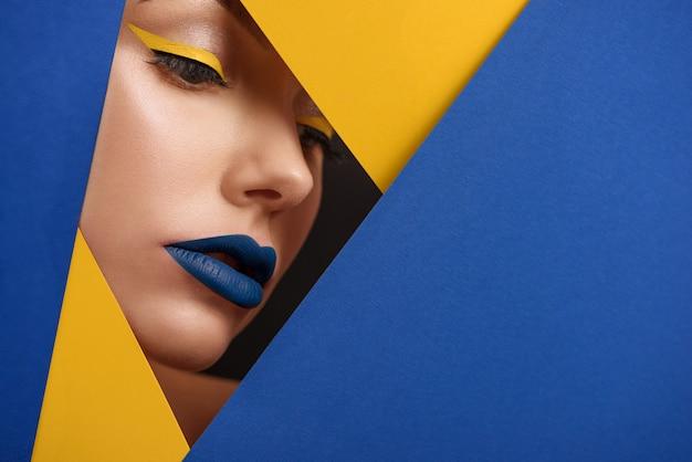 Originele beaty close-up van het gezicht van het meisje omringd door een blauw en geel karton.