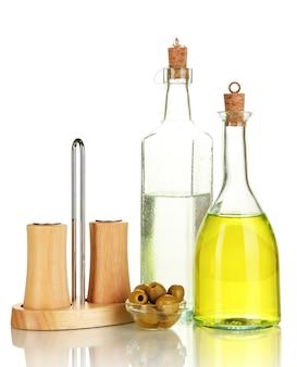Originele glazen flessen met saladedressing op wit wordt geïsoleerd