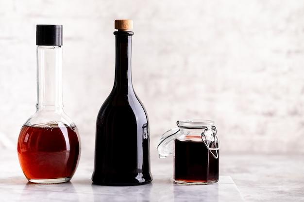 Originele glazen flessen met verschillende azijn op een marmeren tafel tegen een tafel van een witte bakstenen muur. kopieer ruimte. horizontaal.