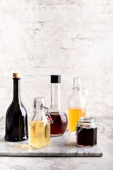 Originele glazen flessen met verschillende azijn op een marmeren tafel tegen een tafel van een witte bakstenen muur. kopieer ruimte. verticaal.