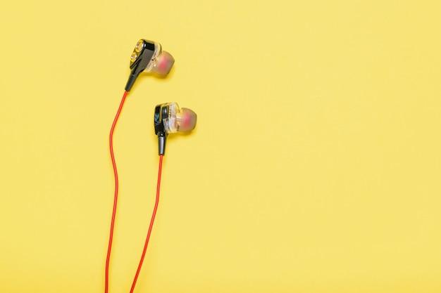 Originele hoofdtelefoon voor smartphone met rode kabel op geel.