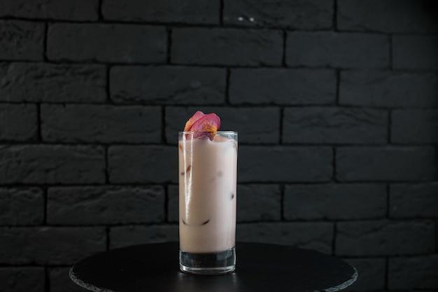 Originele zoete witte milkshake met aardbeiensap met ijsblokjes tonic en wodka op een zwarte tafel in de bar. alcoholische dranken