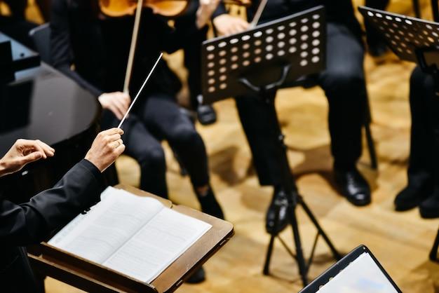 Orkestdirigent van achteren richt zijn muzikanten tijdens een concert.