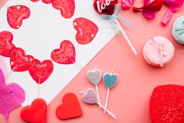 Ornament en geschilderde harten in de buurt van kaarsen en koekjes