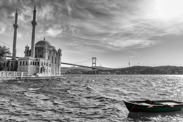 Ortakoy-moskee, de bosporus-brug en een boot bij de pier, zwart-wit beeld, istanbul.