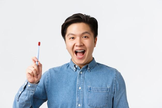 Orthodontie, tandheelkundige zorg en hygiëne concept. glimlachende vrolijke aziatische man die warme, verzorgende tandenbeugels toont, tandenborstel vasthoudt en mond open, tandpasta, witte achtergrond aanbevelen.