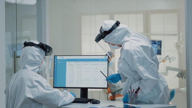 Orthodontische assistent aan het werk op de computer bij de mondelinge kabinet