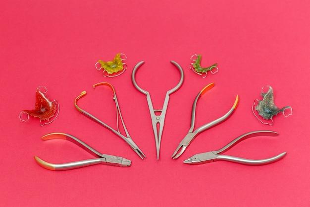 Orthodontische metalen gereedschappen en tandheelkundige beugels of houders op roze