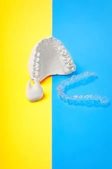 Orthodontische tandheelkundige thema op blauwe en gele achtergrond. transparante onzichtbare tandheelkundige aligners of beugels toepasbaar voor een orthodontische tandheelkundige behandeling