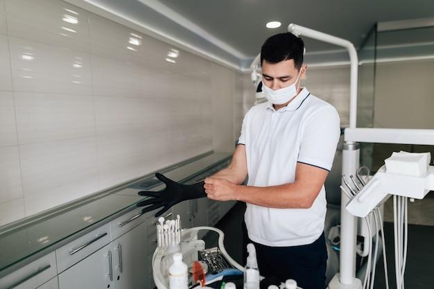Orthodontist die chirurgische handschoenen in bureau zetten