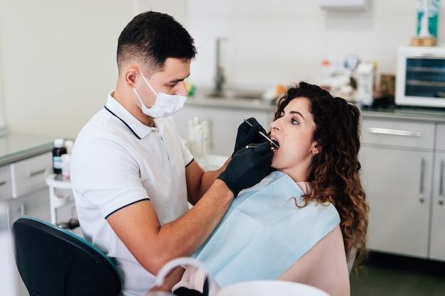 Orthodontist die een controle van patiënt uitvoert