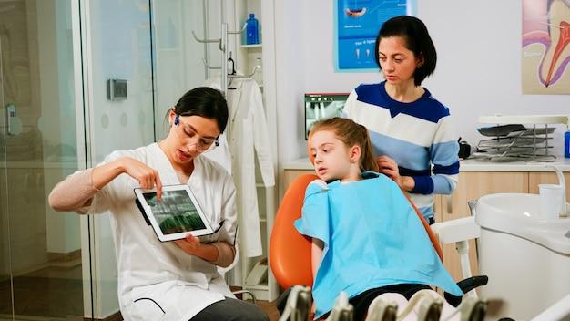 Orthodontist die tablet vasthoudt en röntgenfoto's van de kaak toont aan kleine patiënt terwijl hij tijdens het consult een behandeling voorstelt. stomatologist presenteren aan moeder van meisje tandheelkundige radiografie met behulp van moderne gadget.