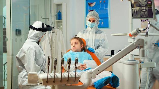 Orthodontist in beschermende overall spreekt met moeder van kindpatiënt met kiespijn tijdens covid-19 in stomatologisch kantoor. concept van nieuw normaal tandartsbezoek bij uitbraak van coronavirus